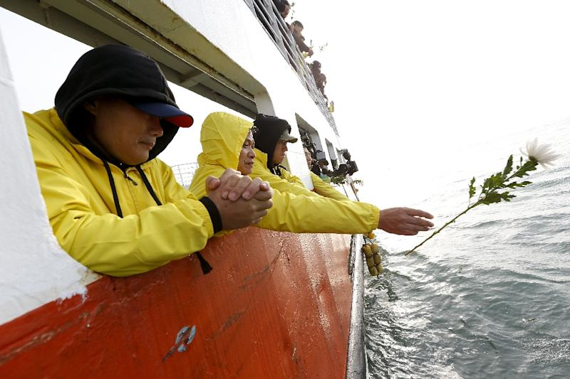 Relatives of victims of the Sewol ferry disaster throw flowers to pay tribute to the victims of the April 16, 2014 sinking, at sea off the coast of South Korea's southern island of Jindo on April 15, 2015