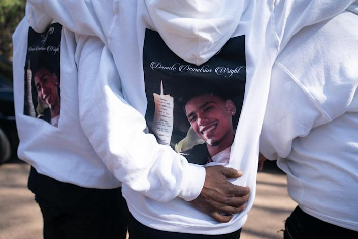 The back of white sweatshirts worn by mourners depict a smiling young man next to a candle