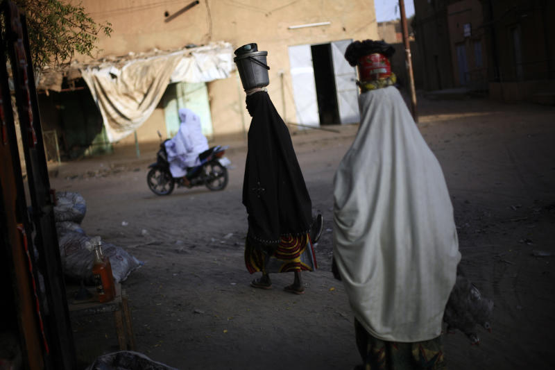 Malian women carry containers on their head as they head out from the market in Gao, northern Mali, Tuesday Feb. 19, 2013. A French soldier has been confirmed dead during a military operation in northern Mali, French President Francois Hollande said on Tuesday(AP Photo/Jerome Delay)