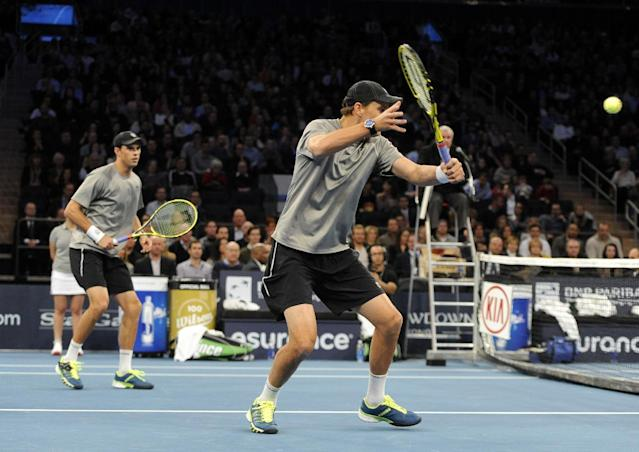Mike Bryan, left, watches his brother, Bob return a shot against Patrick and John McEnroe in the BNP Paribas Showdown Tennis Tournament on Monday, March 3, 2014, in New York. The Bryans won 8-3. (AP Photo/Kathy Kmonicek)