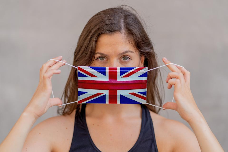 Coronavirus outbreak in UK and worldwide health crisis. Woman wearing UK British flag face mask against infectious diseases 2019 Novel Coronavirus. Conceptual portrait of Protection against Covid-19.