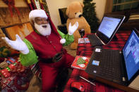Larry Jefferson portrays Santa Claus and conducts a visit via a computer screen with Raquel Anaya and her cousins Lexi and Luna Reyes from his home in Duncanville, Texas, on Dec. 9, 2020. The children lost a grandmother to COVID-19 recently. In this socially distant holiday season, Santa Claus is still coming to towns (and shopping malls) across America but with a few 2020 rules in effect. (AP Photo/LM Otero)
