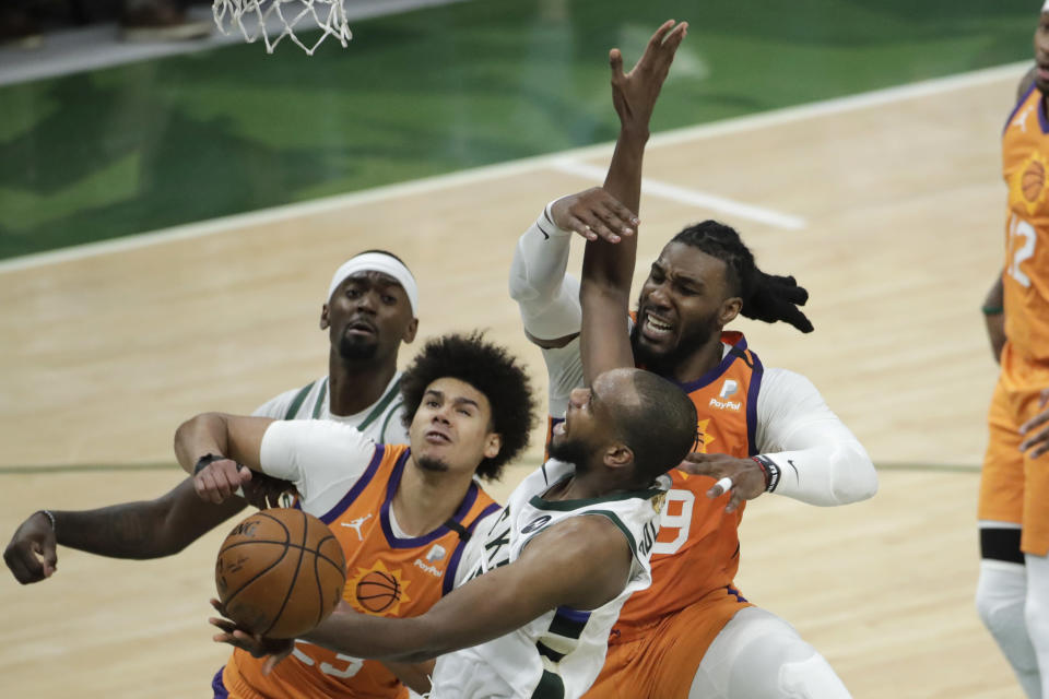Phoenix Suns forward Jae Crowder, right, blocks a shot by Milwaukee Bucks forward Khris Middleton, center, during the second half of Game 4 of basketball's NBA Finals Wednesday, July 14, 2021, in Milwaukee. (AP Photo/Aaron Gash)
