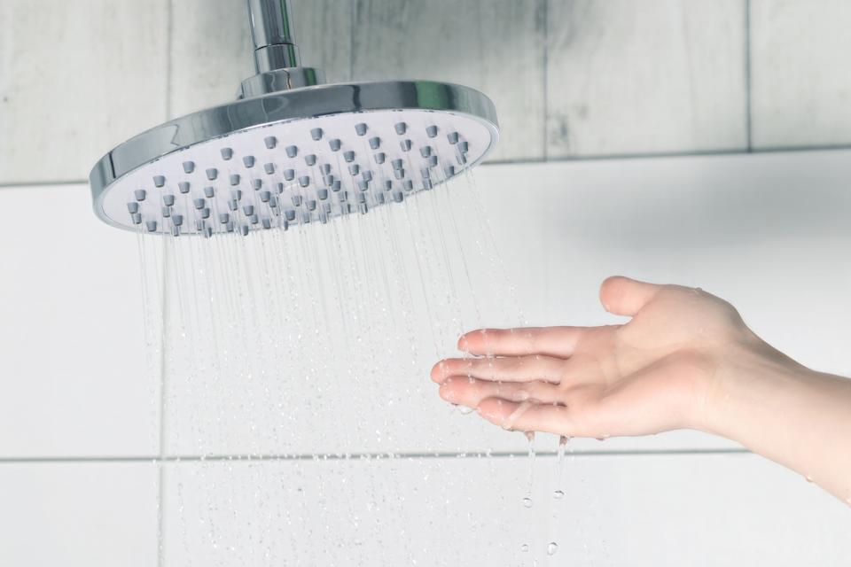 Female hand touching water pouring from a rain shower head, checking water temperature.