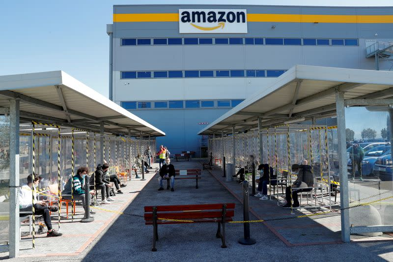 Workers relax during a break outside Amazon's distribution centre in Passo Corese