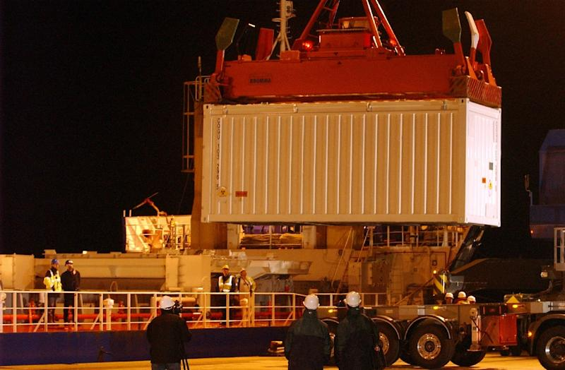 Workers load uranium-plutonium mixed oxide (MOX) civilian fuel made from American military plutonium on a boat heading to the US, at the port in Cherbourg, northern France, on March 22, 2005