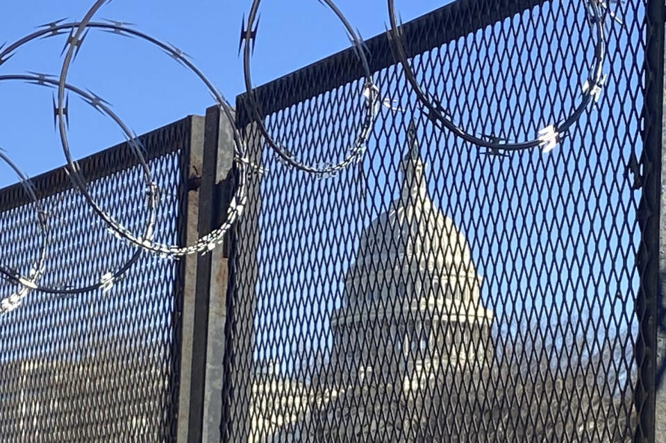 In this Saturday, Jan. 23, 2021 photo, riot fencing and razor wire reinforce the security zone on Capitol Hill in Washington. (AP Photo/Eileen Putman)