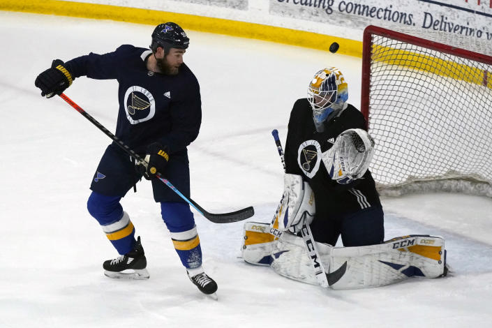 St. Louis Blues' Ryan O'Reilly, left, watches a puck sail over goalie Joel Hofer during NHL hockey training camp Tuesday, Jan. 5, 2021, in Maryland Heights, Mo. (AP Photo/Jeff Roberson)