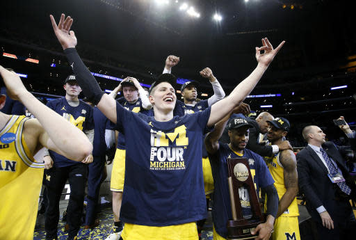 Michigan forward Moritz Wagner, foreground, and teammates celebrate after defeating Florida State 58-54 in an NCAA men's college basketball tournament regional final Saturday, March 24, 2018, in Los Angeles. (AP Photo/Alex Gallardo)