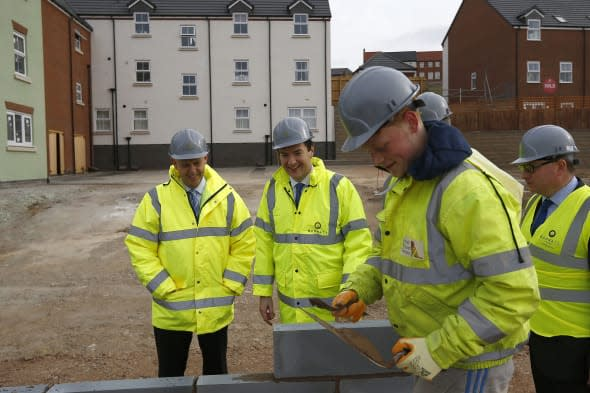 Chancellor of the Exchequer George Osborne watches a trainee lay a block  during a visit to a Barratt Homes building site in Nuneaton, the day after he said in his annual budget that the government would extend the equity loan portion of the Help to Buy scheme for four years longer than planned to 2020, a move he said would deliver 120,000 new homes.
