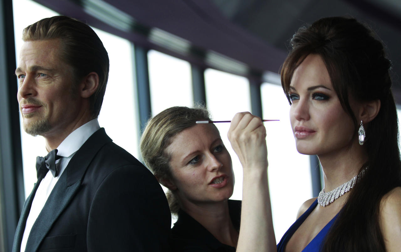 A woman adds make-up to Madame Tussauds wax figures of Angelina Jolie and Brad Pitt at the observation deck of the Sydney Tower Eye in central Sydney March 28, 2012. Madame Tussauds wax museum in Sydney will open its doors on May 2012. REUTERS/Daniel Munoz