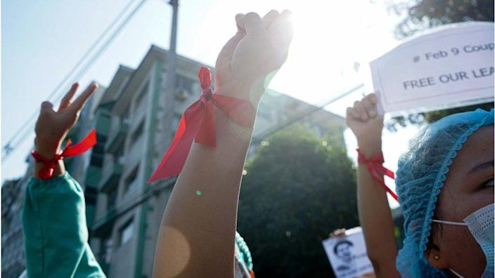 A doctor wearing a red ribbon, raising a flag to show civil disobedience