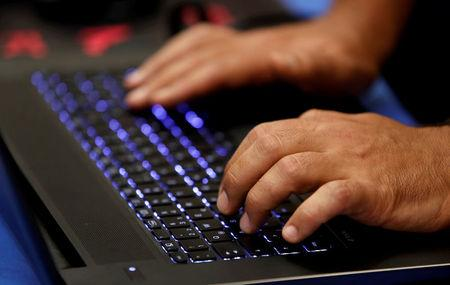FILE PHOTO: A man types into a keyboard during the Def Con hacker convention in Las Vegas, Nevada, U.S. July 29, 2017. REUTERS/Steve Marcus/File Photo