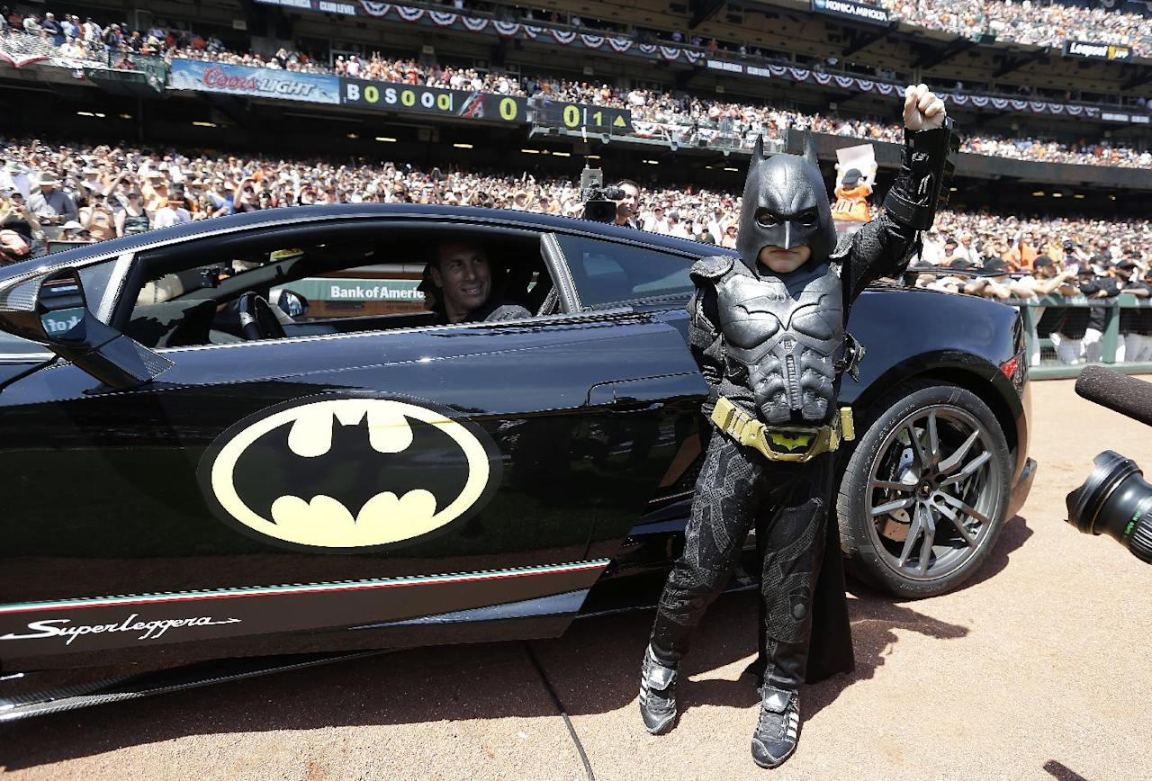 Miles Scott, dressed as Batkid, gestures as he exits the Batmobile to throw the ceremonial first pitch before an opening day baseball game between the San Francisco Giants and the Arizona Diamondbacks in San Francisco, Tuesday, April 8, 2014. On Nov. 15, 2013, Scott, a Northern California boy with leukemia, fought villains and rescued a damsel in distress as a caped crusader through The Greater Bay Area Make-A-Wish Foundation. (AP Photo/Eric Risberg, Pool)
