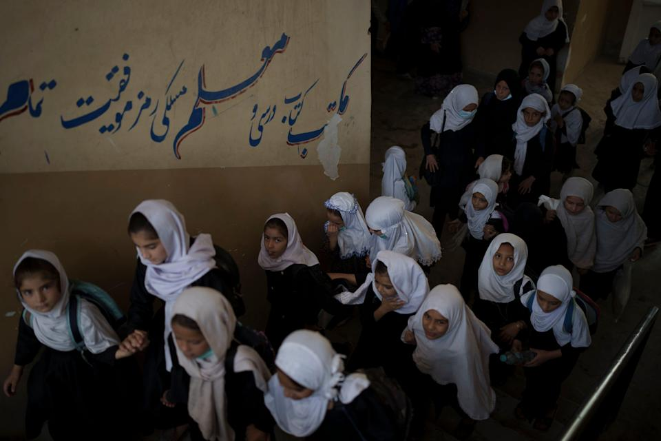 Girls walk upstairs as they enter a school before class in Kabul, Afghanistan, on Sept. 12, 2021.