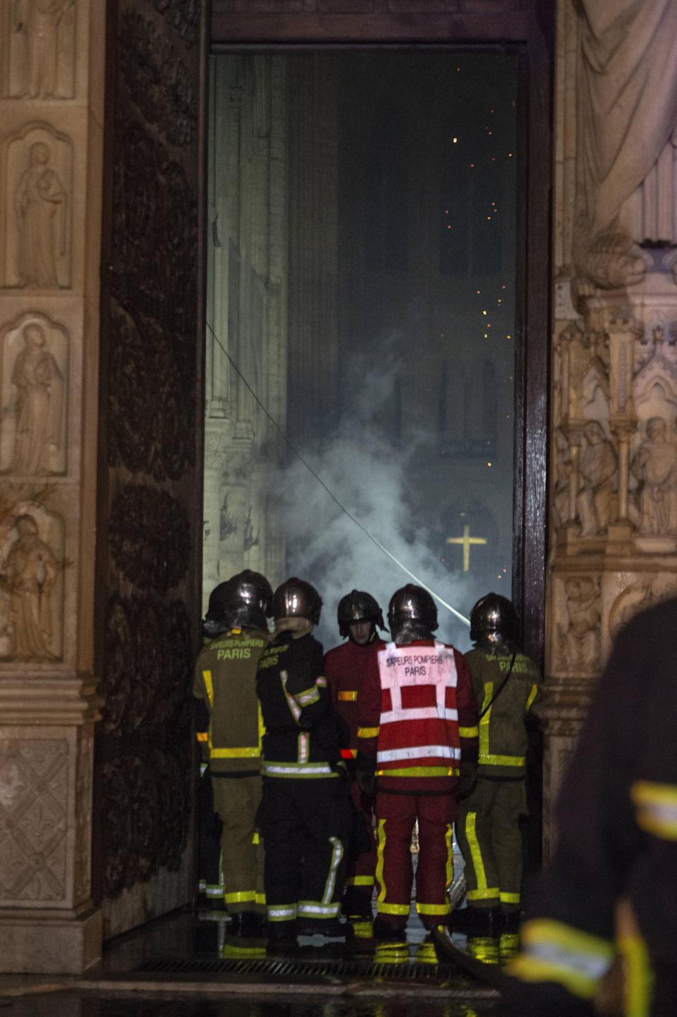 Firefighters assess the damage at Notre Dame cathedral. Source: AAP