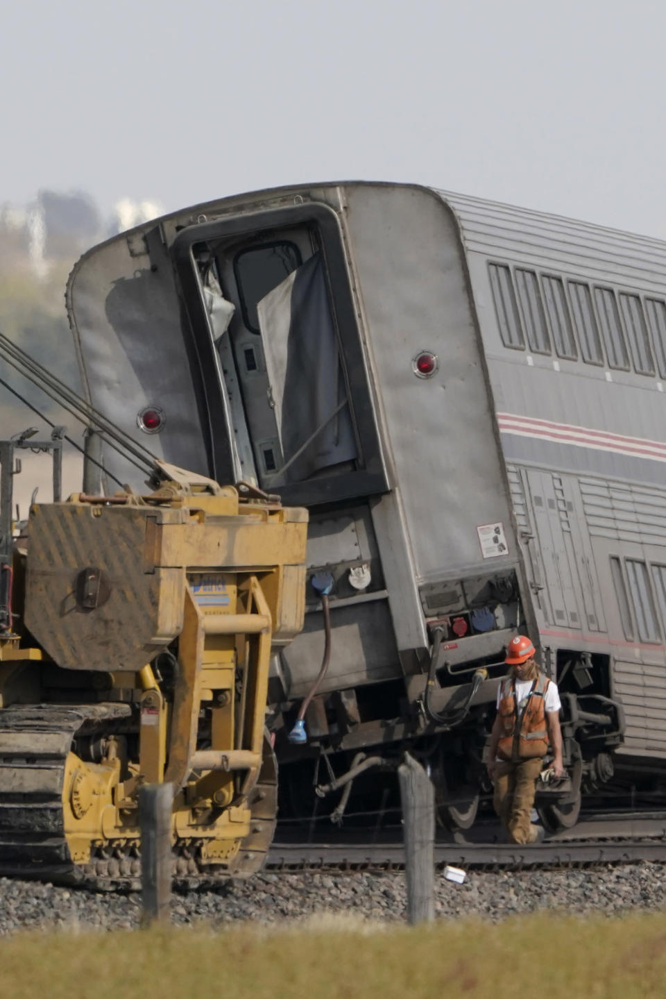 A worker walks Sunday, Sept. 26, 2021, next to a car from an Amtrak train that derailed Saturday just west of Joplin, Mont. The westbound Empire Builder was en route to Seattle from Chicago, with two locomotives and 10 cars. (AP Photo/Ted S. Warren)