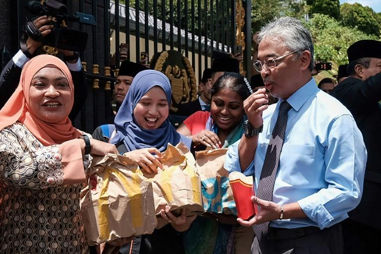 Malaysia's King Sultan Abdullah Sultan Ahmad Shah hands out packages of fast food to reporters camped outside the National Palace. The king is currently meeting members of parliament to ask who they support as premier