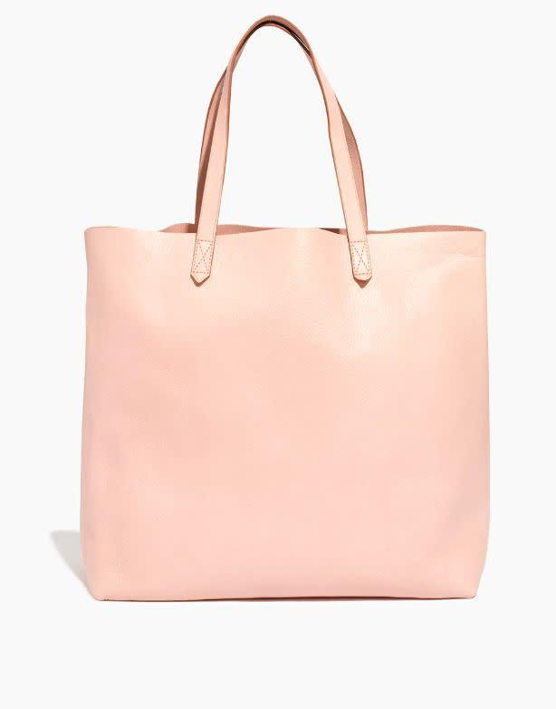 """<strong>Get the <a href=""""https://www.madewell.com/the-transport-tote-F2359.html?dwvar_F2359_color=PK5569&amp;cgid=accessories-bags-tote&amp;position=6&amp;position=6#start=1"""" rel=""""nofollow noopener"""" target=""""_blank"""" data-ylk=""""slk:Madewell Transport Tote in sheer pink"""" class=""""link rapid-noclick-resp"""">Madewell Transport Tote in sheer pink</a> for $168</strong>"""