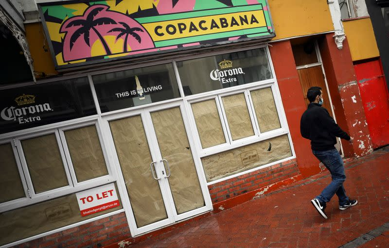 Man walks past a restaurant closed during the COVID-19 outbreak, in Cape Town