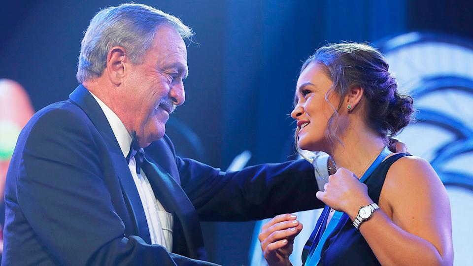 Pictured here, tennis great John Newcombe presents Ash Barty with a medal bearing his own name.