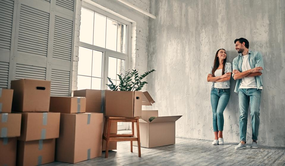 Couple on moving day. Attractive young woman and handsome bearded man with cardboard moving boxes are happy to move into new home.