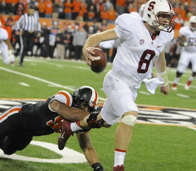 Oregon State's Scott Crighton (95) grabs Stanford's quarterback Kevin Hogan (8) during the first half of an NCAA college football game in Corvallis, Ore., Saturday Oct. 26, 2013. (AP Photo/Greg Wahl-Stephens)