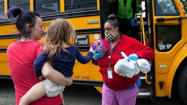 PHOTO: Bus driver Treva White and nutritionist Shaunte Fields deliver meals to children and their families on May 6, 2020, in Seattle. (Karen Ducey/Getty Images)