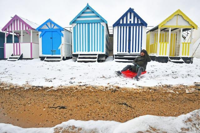 Beach huts next to a snow-covered beach in Essex