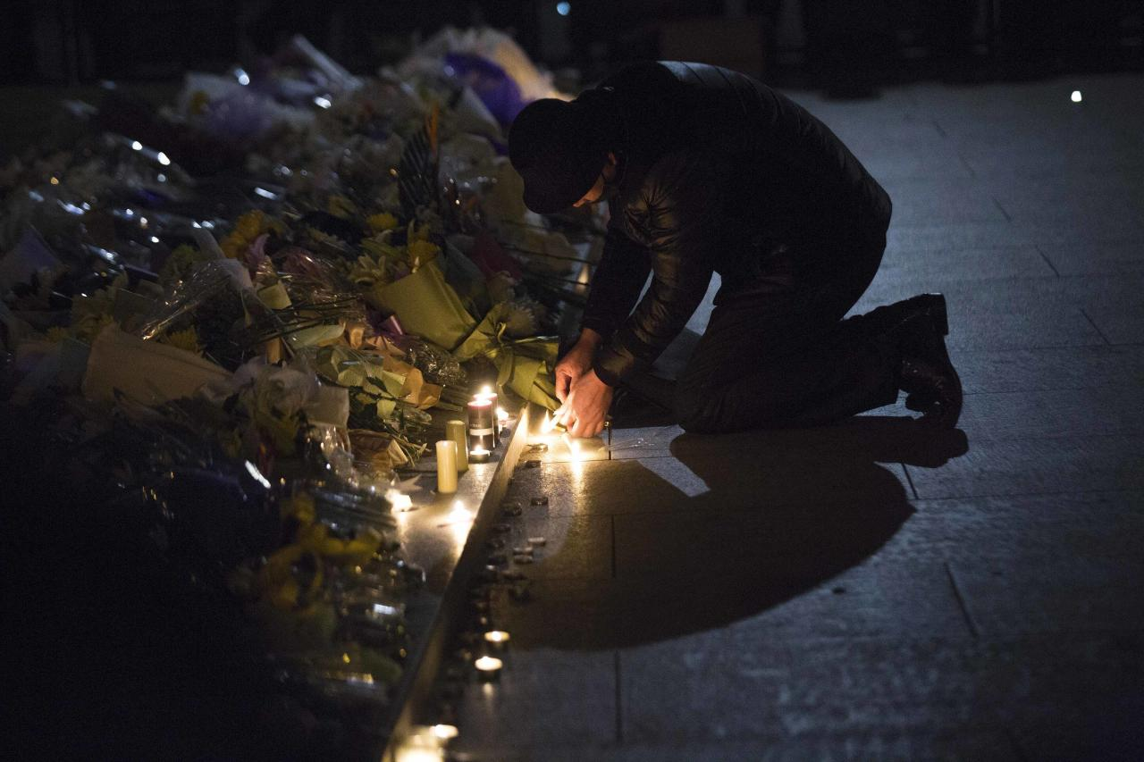 A man lights candles during a memorial ceremony for people who were killed in a stampede incident during a New Year's celebration on the Bund, in Shanghai January 1, 2015. The stampede killed at least 36 people, authorities said, possibly caused by people rushing to pick up fake money thrown from a building overlooking the city's famous Bund waterfront district. REUTERS/Aly Song (CHINA - Tags: DISASTER SOCIETY)
