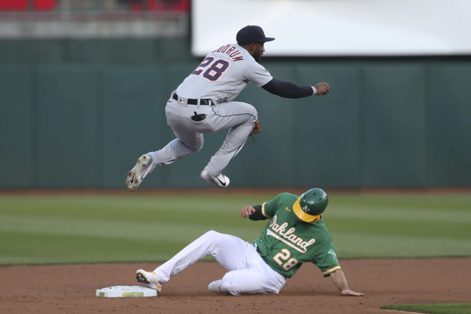Oakland Athletics' Matt Olson, right, slides into second as Detroit Tigers' Niko Goodrum throws to first on a ball hit by Matt Chapman, who was safe during the second inning of a baseball game in Oakland, Calif., Friday, April 16, 2021. (AP Photo/Jed Jacobsohn)