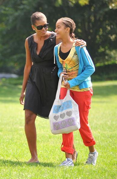 First lady Michelle Obama walks with her daughter, Malia Obama as they walk across the South Lawn upon their return to the White House September 6, 2009 in Washington, DC. The first family was vacationing at Camp David. (Photo by Ron Sachs-Pool via Getty Images)