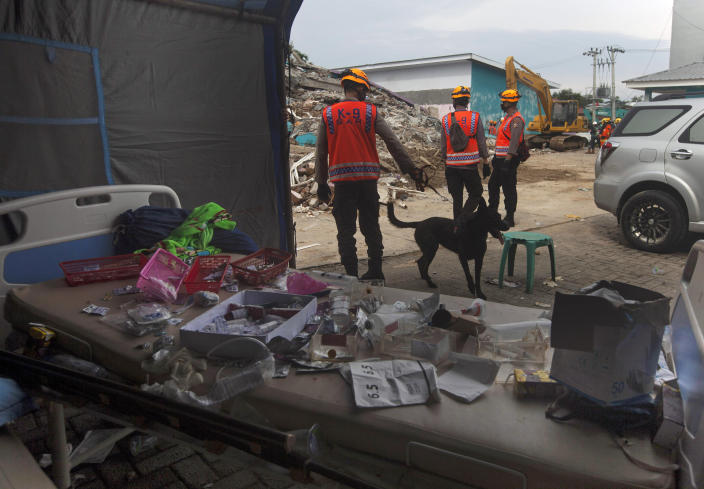 Members of police K-9 squad lead a sniffer dog during a search for victims at a hospital building collapsed in Friday's earthquake in Mamuju, West Sulawesi, Indonesia, Sunday, Jan. 17, 2021. Rescuers retrieved more bodies from the rubble of homes and buildings toppled by the 6.2 magnitude earthquake while military engineers managed to reopen ruptured roads to clear access for relief goods. (AP Photo/Yusuf Wahil)