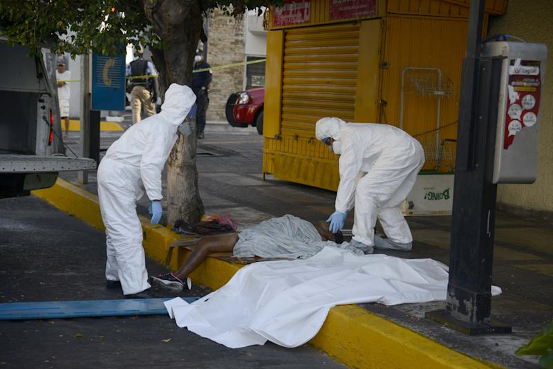 TOPSHOT - EDITORS NOTE: Graphic content / A corpse of a homeless man, suspected of having the COVID-19 coronavirus, is removed by forensic workers in Acapulco, Mexico, on April 23, 2020. (Photo by FRANCISCO ROBLES / AFP) (Photo by FRANCISCO ROBLES/AFP via Getty Images)
