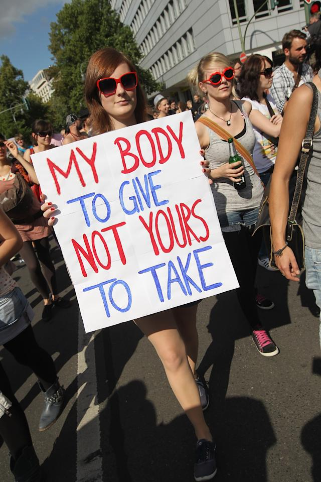 "BERLIN, GERMANY - AUGUST 13:  A young woman holding a sign that reads: ""My Body To Give Not Yours To Take"" participates in the ""Slut Walk"" march on August 13, 2011 in Berlin, Germany. Several thousand men and women turned out to protest against rape and a woman's right to her body.  (Photo by Sean Gallup/Getty Images)"
