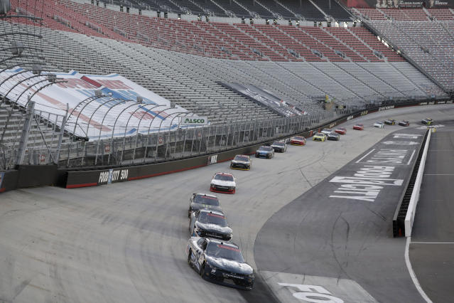 Drivers make their way around the track past empty stands during a NASCAR Xfinity Series auto race at Bristol Motor Speedway Monday, June 1, 2020, in Bristol, Tenn. The race is being run without fans in the stands due to the coronavirus outbreak. (AP Photo/Mark Humphrey)