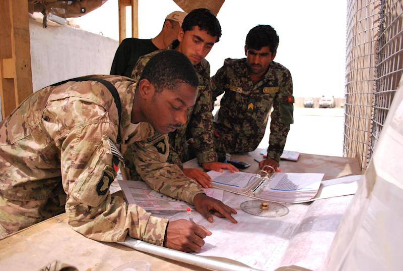 In a Sunday, May 19, 2013, photo U.S. Army Sgt. Carrinton Peterson, 23, left, of Killen, Texas, assigned to the 101st Airborne Division in the Shinwar District of Nangarhar Province, trains two Afghan National Army soldiers  to plot a target for their D-30 Howitzers. U.S. Army advisers are working to support the Afghan military as they take control of security ahead of the 2014 drawdown of U.S. forces. (AP Photo/Kristin M. Hall)