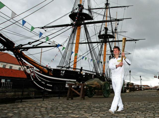 Jamie Poole walks alongside HMS Trincomalee as he carries the Olympic Flame on the Torch Relay leg through Hartlepool.