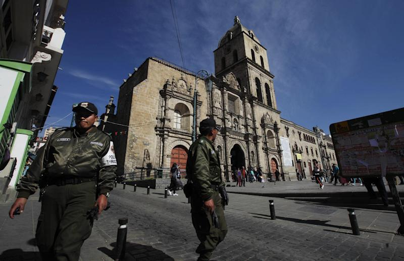 In this Aug. 6, 2013 file photo, police patrol near the San Francisco Basilica in La Paz, Bolivia. Cultural officials in the Andes have long struggled to protect Incan and pre-Columbian cultural treasures. Now, colonial sacred art has become a similar worry. By law, both are national patrimony and exporting them is illegal. (AP Photo/Juan Karita)