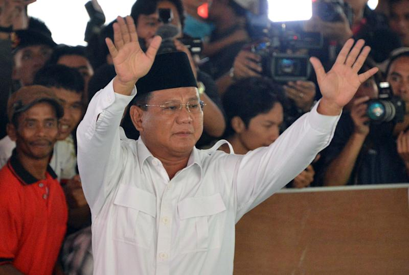 Indonesian presidential candidate Prabowo Subianto (centre) waves to supporters and the media as he arrives to vote at the village of Bojong Koneng in Bogor, West Java province, on July 9, 2014