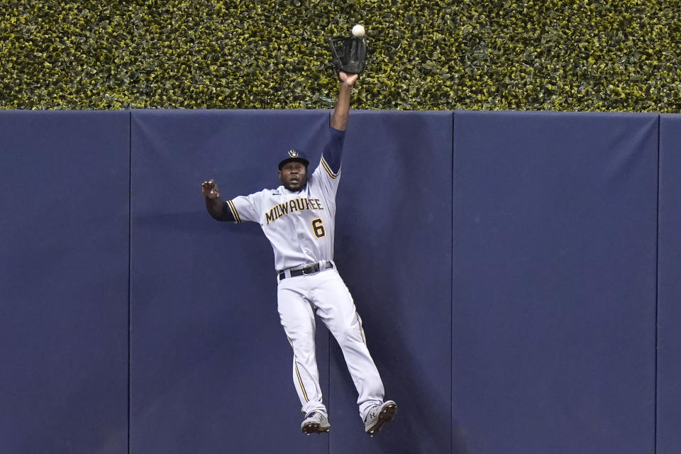 Milwaukee Brewers center fielder Lorenzo Cain (6) can't make the catch on a solo home run hit by Miami Marlins' Miguel Rojas during the first inning of a baseball game, Saturday, May 8, 2021, in Miami. (AP Photo/Lynne Sladky)