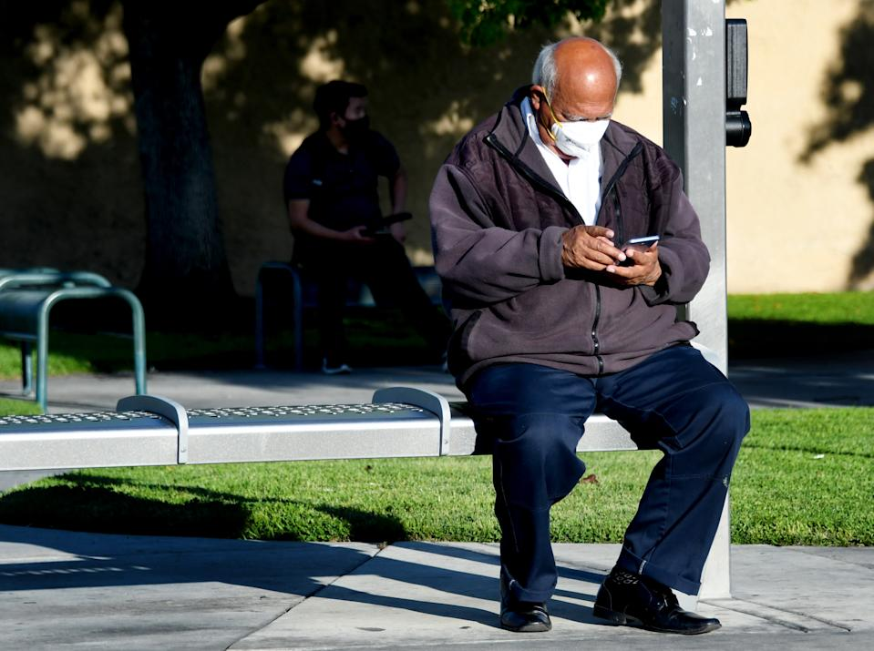 BELL, CA - APRIL 14:  A man wearing a mask during to the Coronavirus Pandemic waits looks at his phone as he waits for a bus along Atlantic Ave. in Bell on Tuesday, April 14, 2020. (Photo by Keith Birmingham/MediaNews Group/Pasadena Star-News via Getty Images)