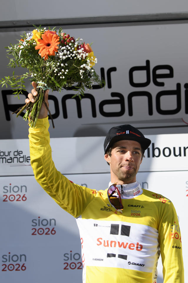 The overall leader Michael Matthews from Australia of team Sunweb celebrates on the podium with the yellow jersey after the prologue, a 4,02 km time trial at the 72nd Tour de Romandie UCI ProTour cycling race in Fribourg, Switzerland, Tuesday, April 24, 2018. (Jean-Christophe Bott/Keystone via AP)
