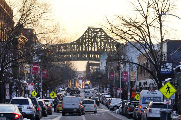 Tobin Bridge frames Broadway as traffic moves in downtown Chelsea, Mass., Feb. 10, 2021. Two predominantly Latino cities in neighboring states have had diverging fates in the global rollout of the coronavirus vaccine. Central Falls, R.I., and Chelsea, have been the states' hardest-hit communities in the pandemic. Public health experts, civil rights groups and immigrant activists have complained for months that Massachusetts isn't doing nearly enough to ensure that Black and Latino residents are inoculated. (AP Photo/Elise Amendola)