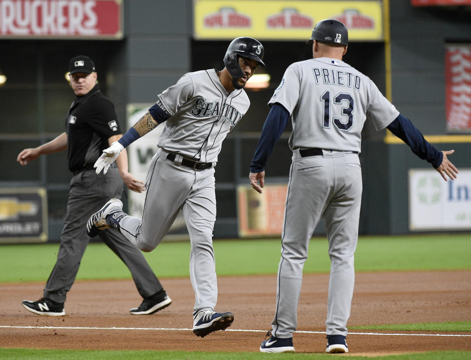 Seattle Mariners' J.P. Crawford, center, celebrates his solo home run off Houston Astros starting pitcher Gerrit Cole with third base coach Chris Prieto (13) during the first inning of a baseball game, Sunday, June 30, 2019, in Houston. (AP Photo/Eric Christian Smith)