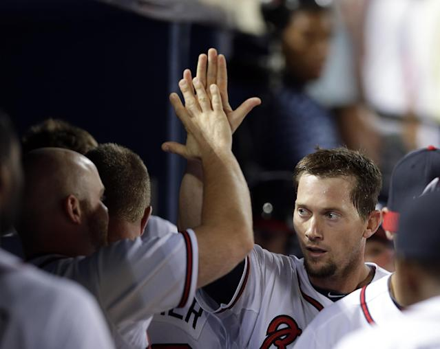 Atlanta Braves' Chris Johnson, center, celebrates after scoring on a Dan Uggla double in the fifth inning of a baseball game against the Colorado Rockies in Atlanta, Monday, July 29, 2013. (AP Photo/John Bazemore)