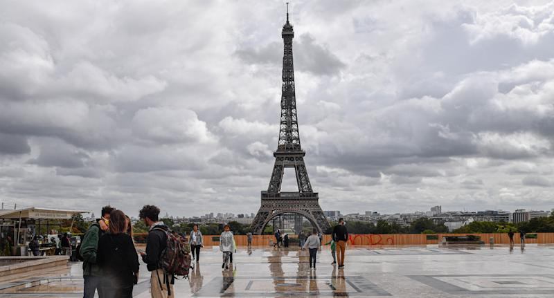Photo shows people in the foreground of the Eiffel Tower in Paris, France.
