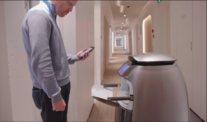Alibaba's FlyZoo robot is shown bringing an item to a guest in the hotel.