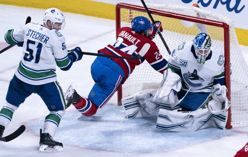 Montreal Canadiens' Phillip Danault is shoved into Vancouver Canucks goaltender Thatcher Demko's net by defenseman Troy Stecher during the second period of an NHL hockey game Tuesday, Feb. 25, 2020, in Montreal. (Paul Chiasson/The Canadian Press via AP)