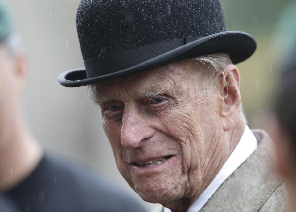 Britain's Prince Philip, in his role as Captain General of the Royal Marines, talks to troops as he attends a Parade on the forecourt of Buckingham Palace, in central London, as it rains Wednesday Aug. 2, 2017.  The 96-year-old husband of Britain's Queen Elizabeth II, Prince Philip made his final solo appearance to mark the finale of the Royal Marines Charity, 1664 Global Challenge. (Yui Mok / Pool via AP)